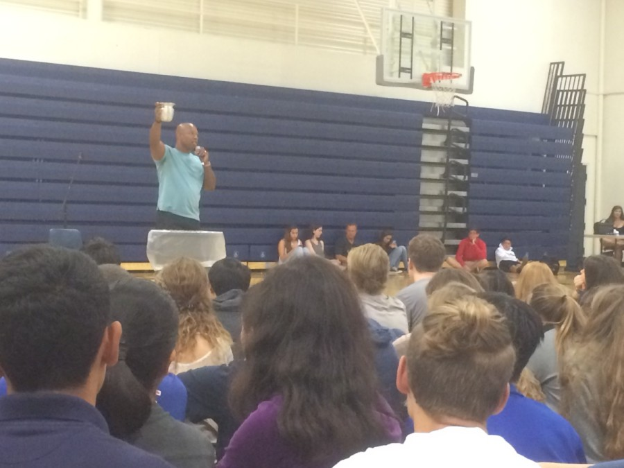 Raising his glass, Keith Hawkins finalizes his speech at Carlmont High School.