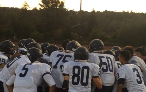 Carlmont Scots huddle together before they charge onto the field.