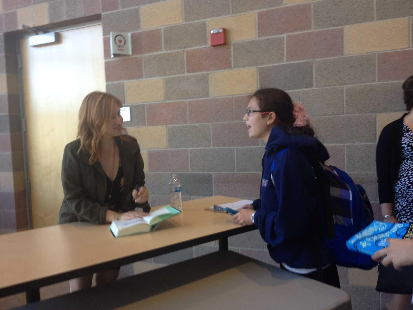 Freshman Alyssa Higdon meets Schneider after the book talk to get Schneider's autograph.