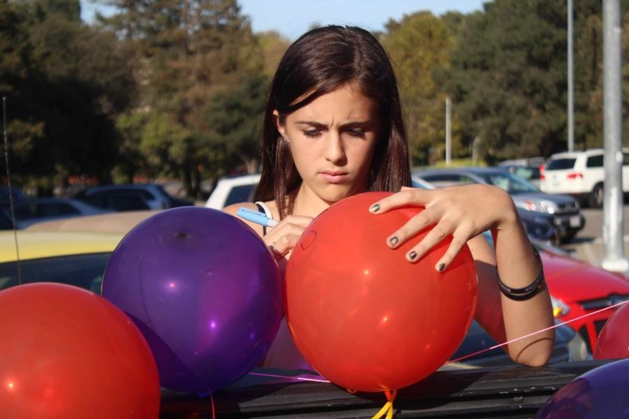 Freshman Suzy Floersch draws out a Mickey Mouse on the balloon at the senior parking lot.