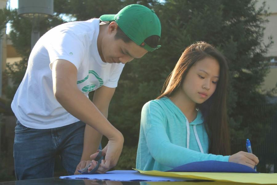 Juniors TJ Amigleo and Jessica Chang cut out colorful feathers for Kevin the bird from the Disney movie