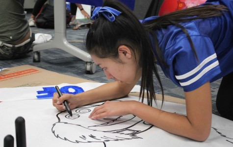Junior Miranda Wong traces her drawing of Dug to enhance the lines.