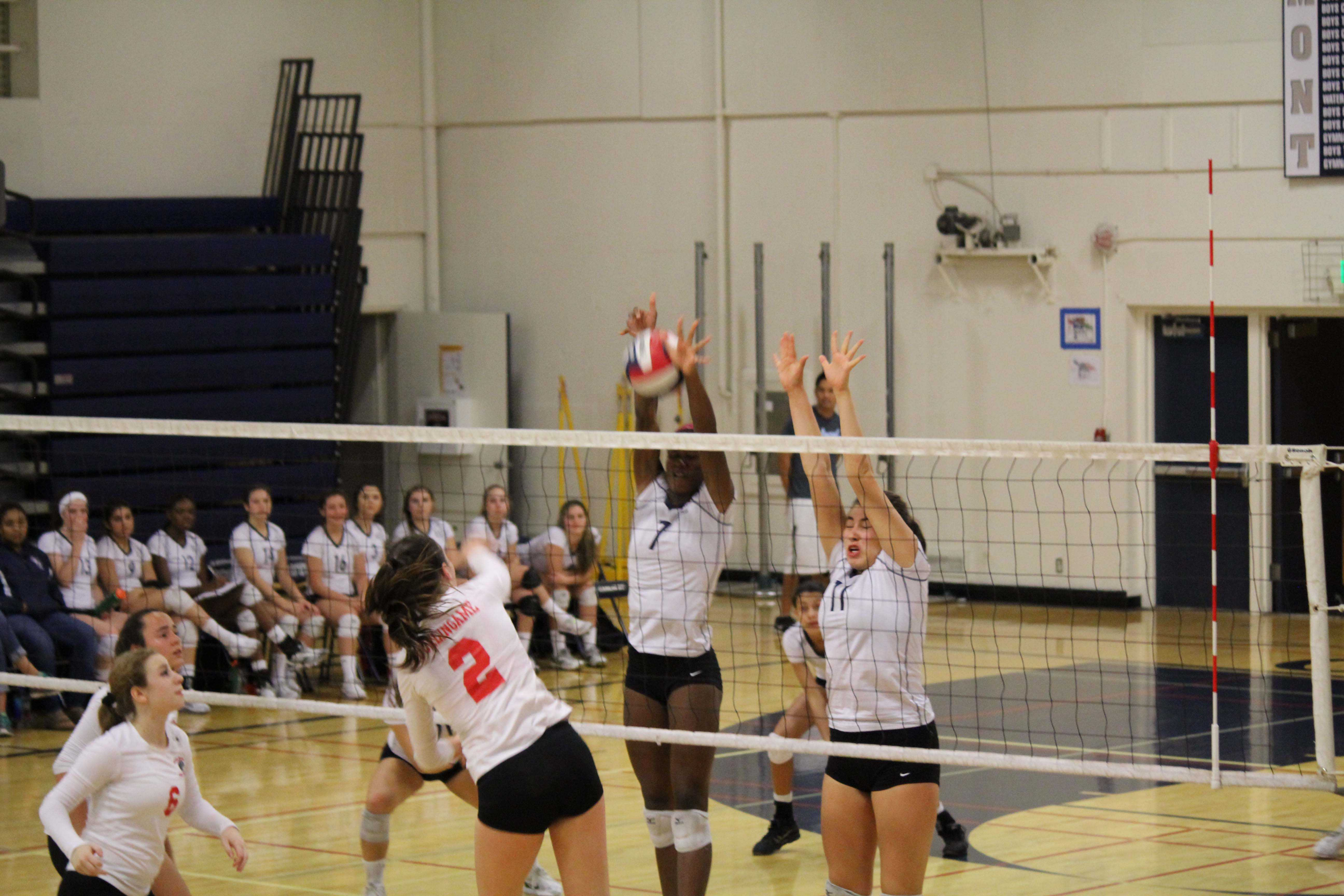 Alexis Morrow (7)  and Mia Hogan (11) leap high as the they block a hit from The Panthers