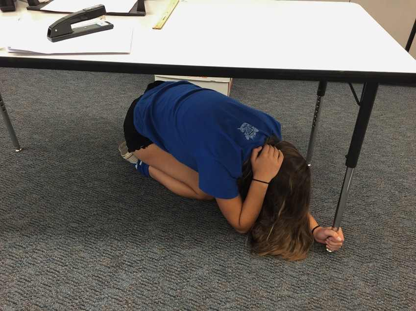 Sophomore Cate Armstrong practices earthquake procedures.