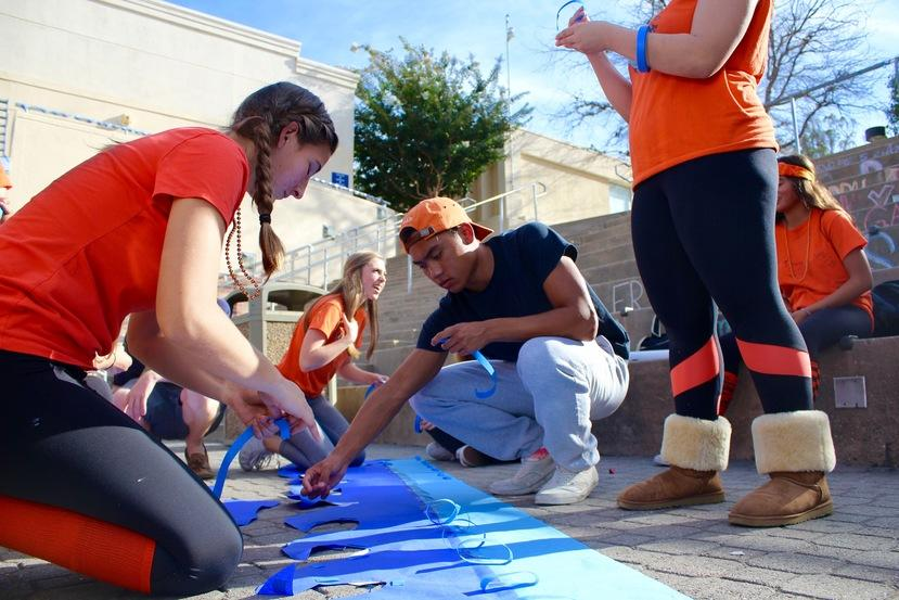 Homecoming nominees Cate Armstrong and Josh Camerino help tape decorations onto the sophomore class float.