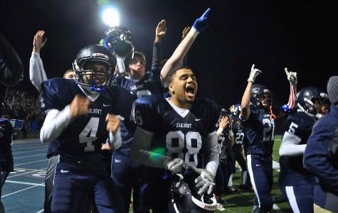 Varsity players on the sideline celebrate as senior Jake Kumamoto attempts to make a touchdown.
