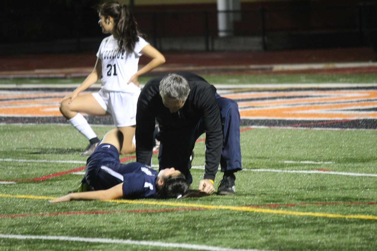 Coach Scott Pendleton checks freshman Kaylee Leong after she was injured by a slide tackle made by one of the Wildcats.