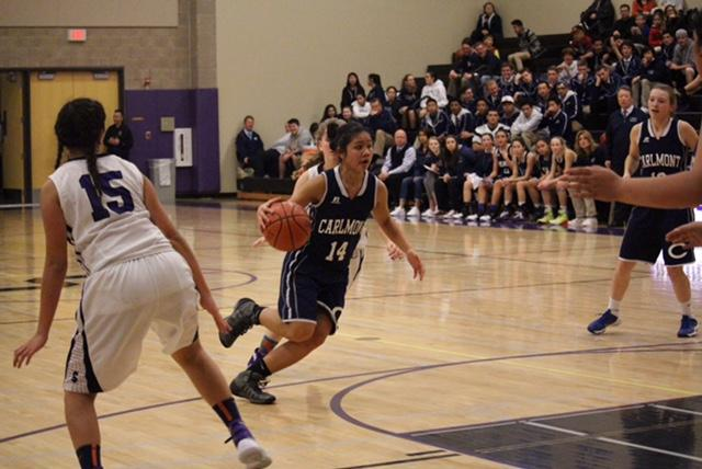 Junior Alexa Bayangos dribbles the ball down the middle of the key.