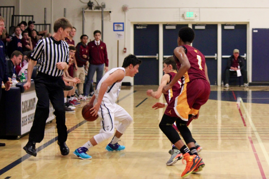 Senior Tyler Brandenburg dribbles the ball away from the Menlo-Atherton players.