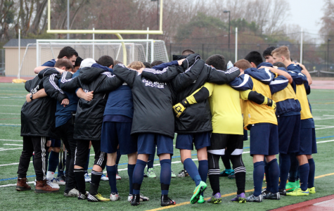 The players and coaches put their arms around each other during a pre-game pep talk.