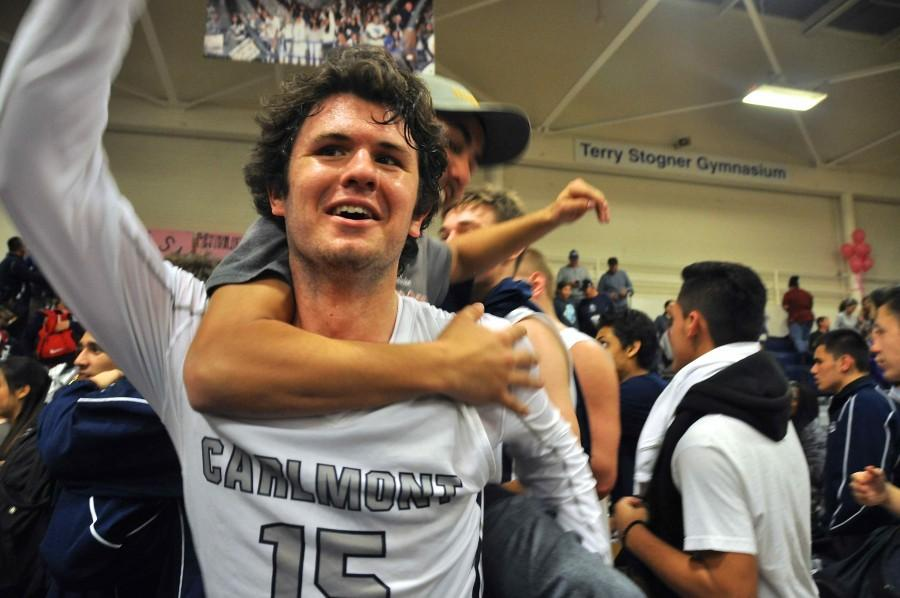 The Screamin' Scots crowd around senior Glenn Smyth and the team to celebrate Carlmont's 51-29 victory.