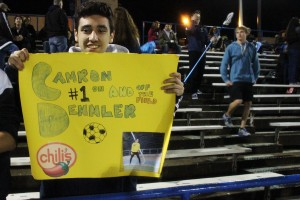 Senior Mario Valenzuela holds up his sign for Dennler, decorated with motivational words and pictures.
