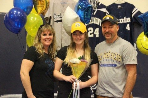 Senior Jacey Phipps smiles with her parents as they all wear San Jose State University apparel.