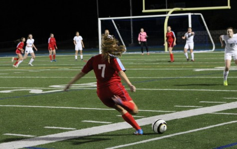 A Hillsdale player takes a free kick after a foul from a Carlmont player in the JV girls soccer game.