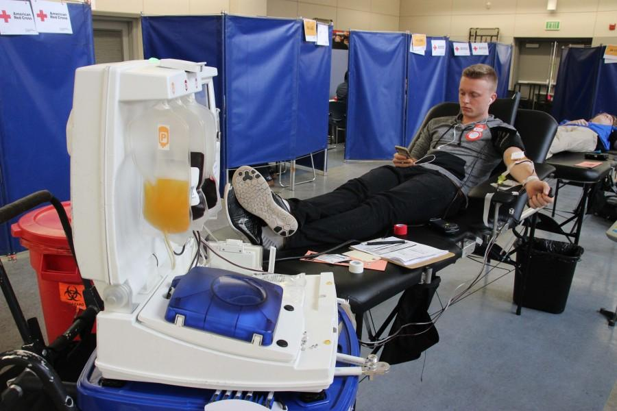 While getting his blood drawn, senior Sergiy Holmer listens to music to distract himself. There was an increase of 15 donors between the first and second blood drive.