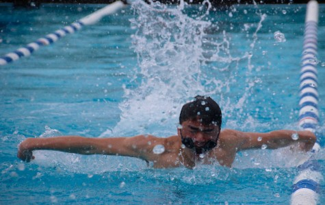 Freshman Nathaniel Pon veers into the lane line as he struggles to swim with his goggles slipping off.