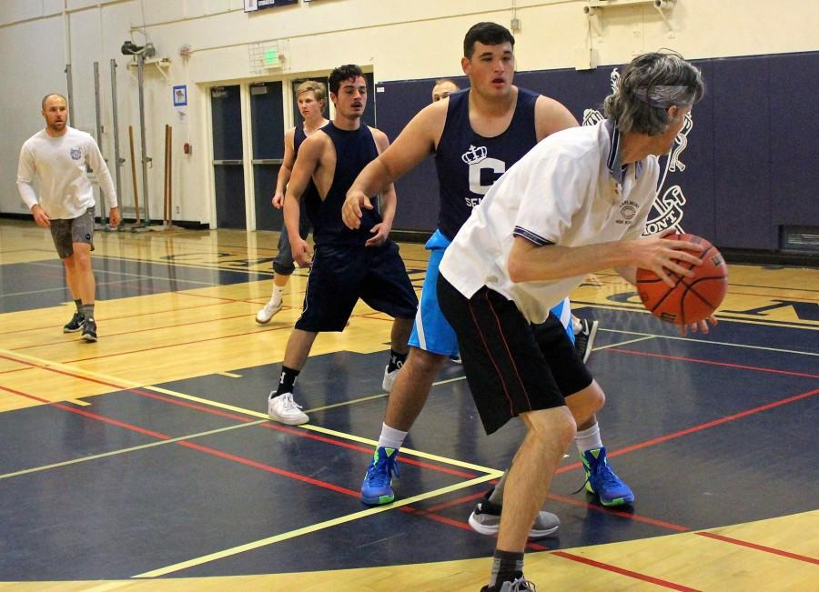 Science+teacher+Josh+Engberg+guards+the+ball+from+senior+Sam+Levy+at+the+start+of+the+2016+student-staff+basketball+game.+