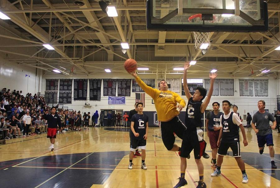 Senior Evan Lee attempts to stop the staff from scoring a basket.