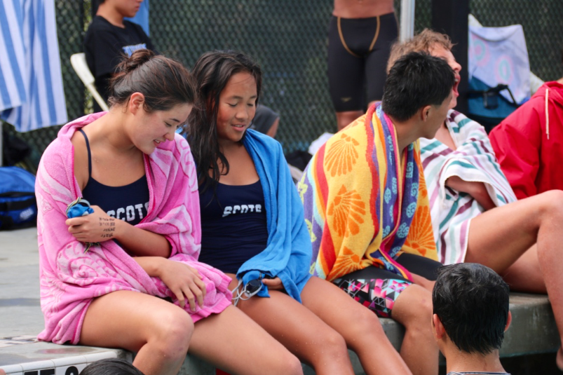 Freshmen+Jade+Margolis+and+Karen+Li+rest+and+try+to+keep+warm+while+they+wait+for+their+race+to+begin.