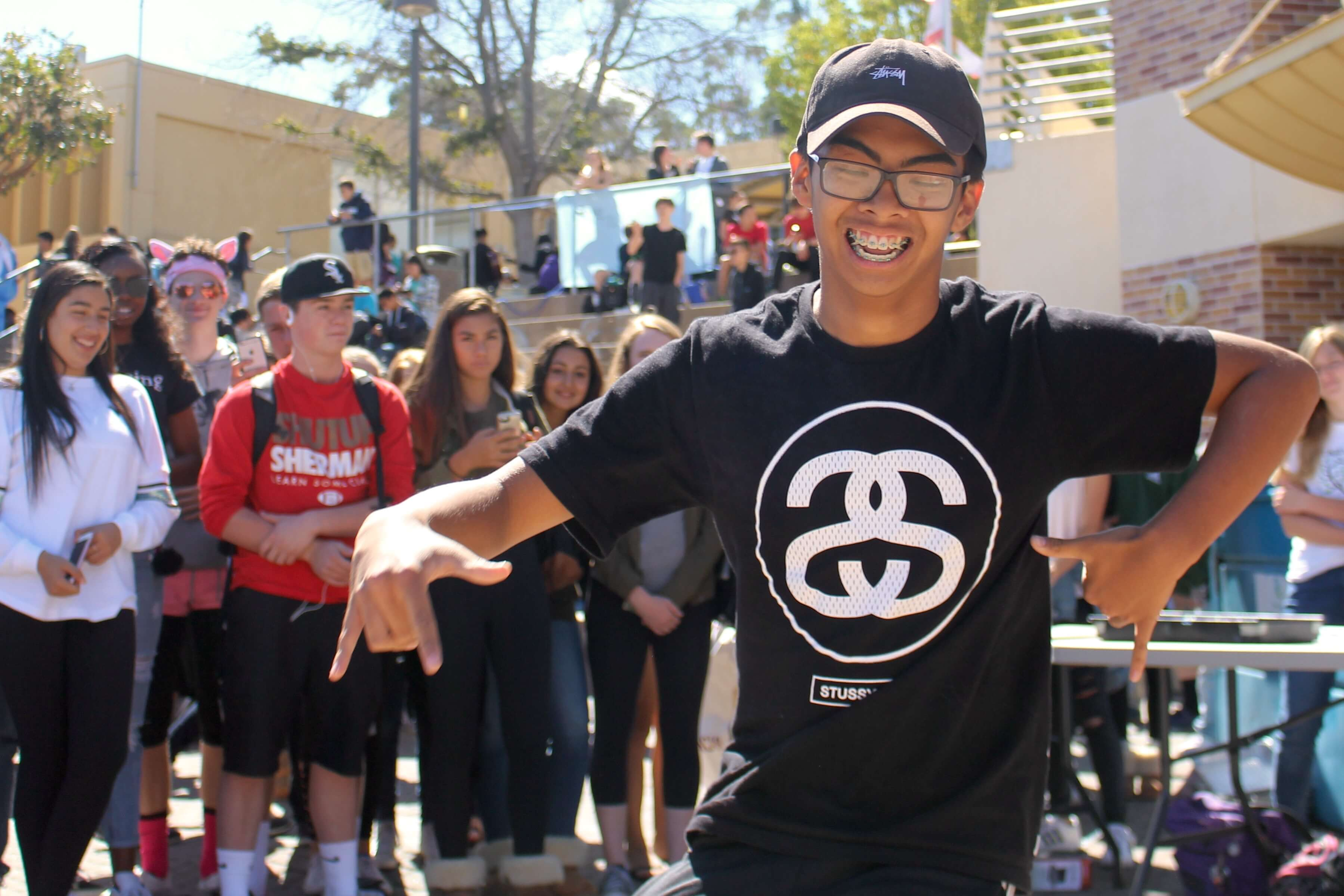 Students gather around the quad while junior Miguel Encarnacion dances to the music.