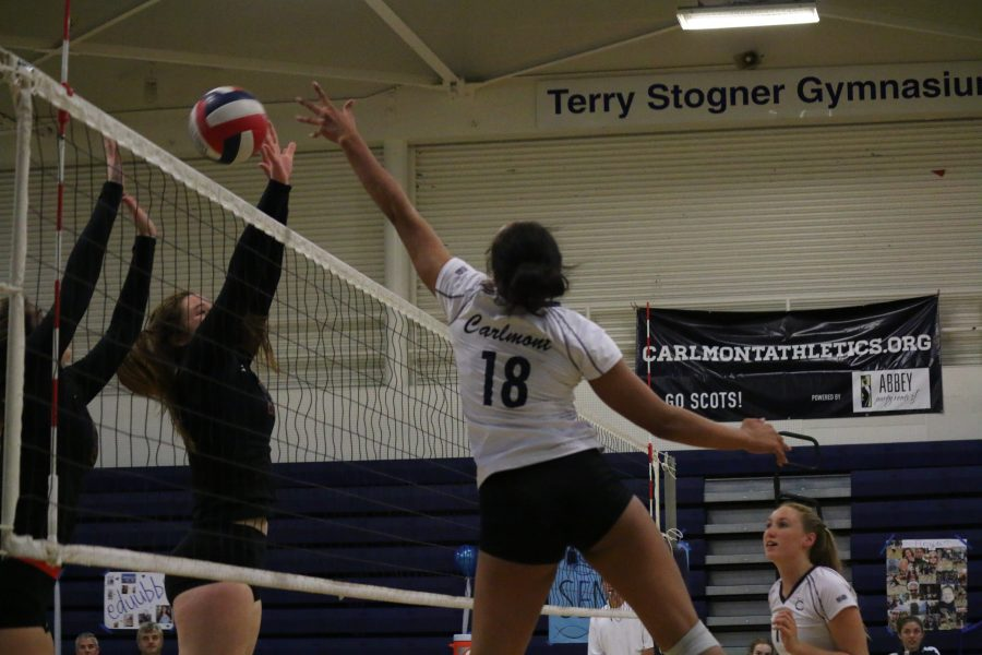 Freshman+Morgan+McClellan+leaps+into+the+air+to+tip+the+ball+over+the+Cougars%27+right+side+hitter.