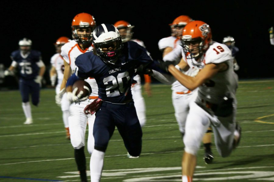 Tailback+Devon+Sagon+deflects+his+San+Mateo+opponent+as+he+carries+the+ball+down+the+field+for+a+first+down.