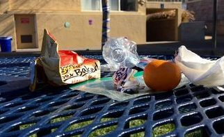 A pile of trash accumulates on a campus table over the course of a school day.