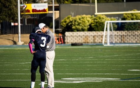 Quarterback, Simon Tara, discusses the game plan with coach, Bruce Douglas during a timeout.