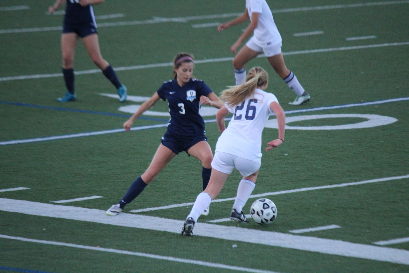 11th grader Lauren Morris dribbles the ball up the sideline.