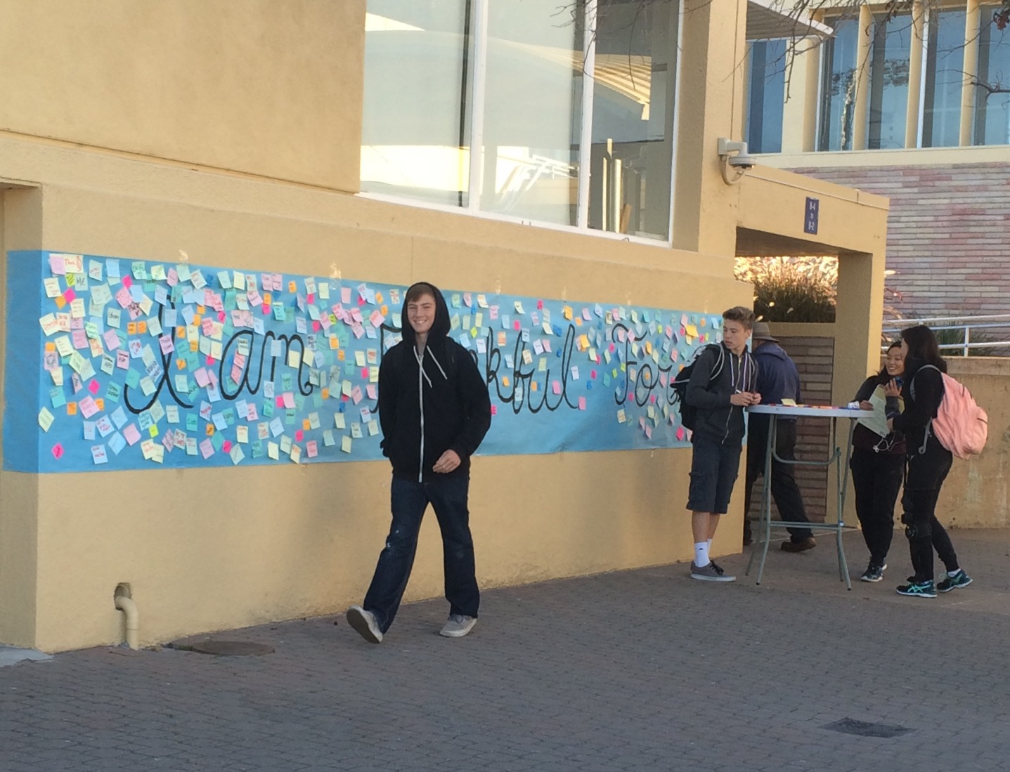 Students add to and walk by a mural that reads
