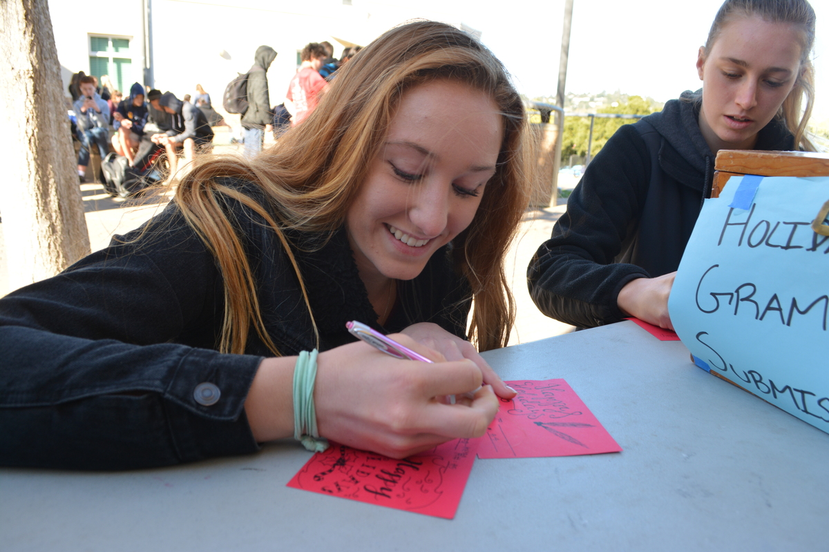 Emma Vanoncini, a junior, writes a handwritten note on a holiday gram for her friend.