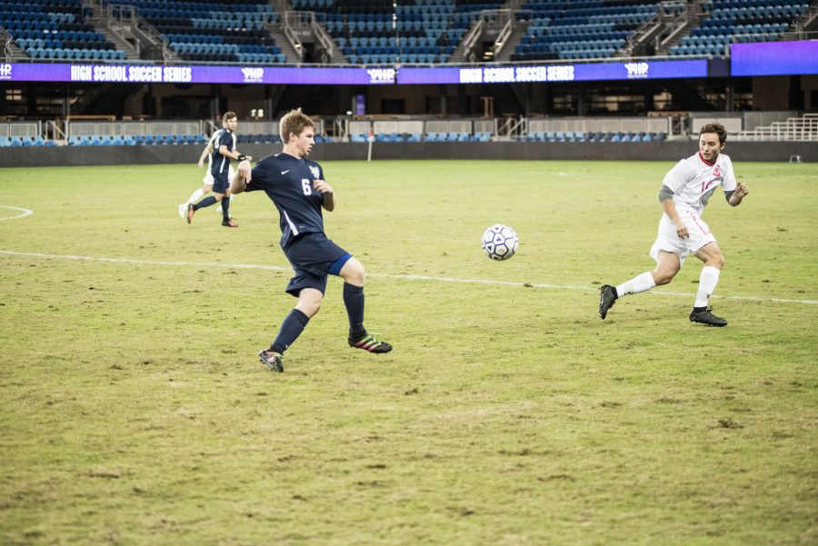 Ben Zaino, a junior, crosses the ball to another teammate.
