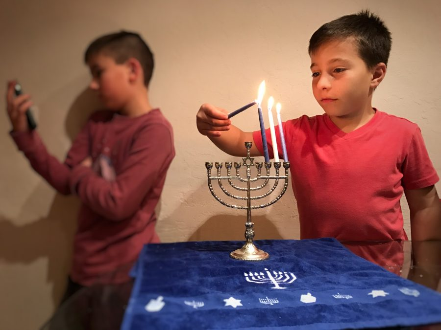 A+9-year-old+boy+is+lighting+a+Menorah+while+the+other+is+in+the+back+on+a+device+because+he+doesn%E2%80%99t+find+it+important.+%0A
