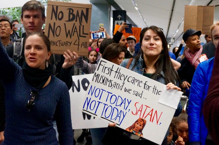 Crowds gathered in the International Terminal's arrival area and voiced their opinions through clever signs and posters.