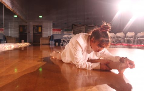 Stephanie Ramos, a senior, concentrates on stretching before the winter show, making sure that she is warmed up and ready to get on stage.