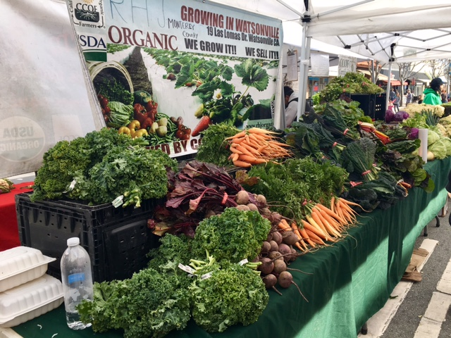 A+produce+vendor+displays+their+fresh+produce+for+people+to+purchase.
