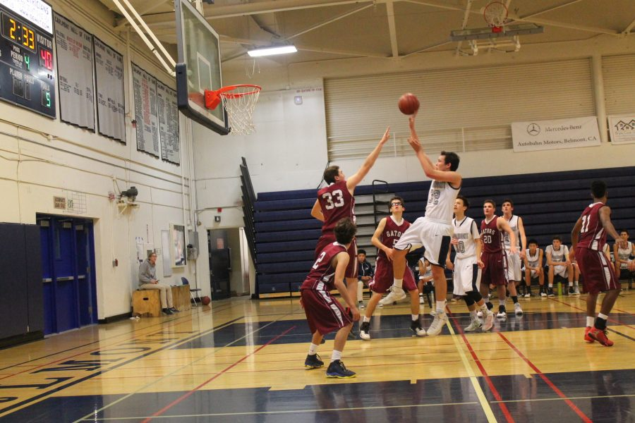 Sophomore Grant Acker leaps over a defender.