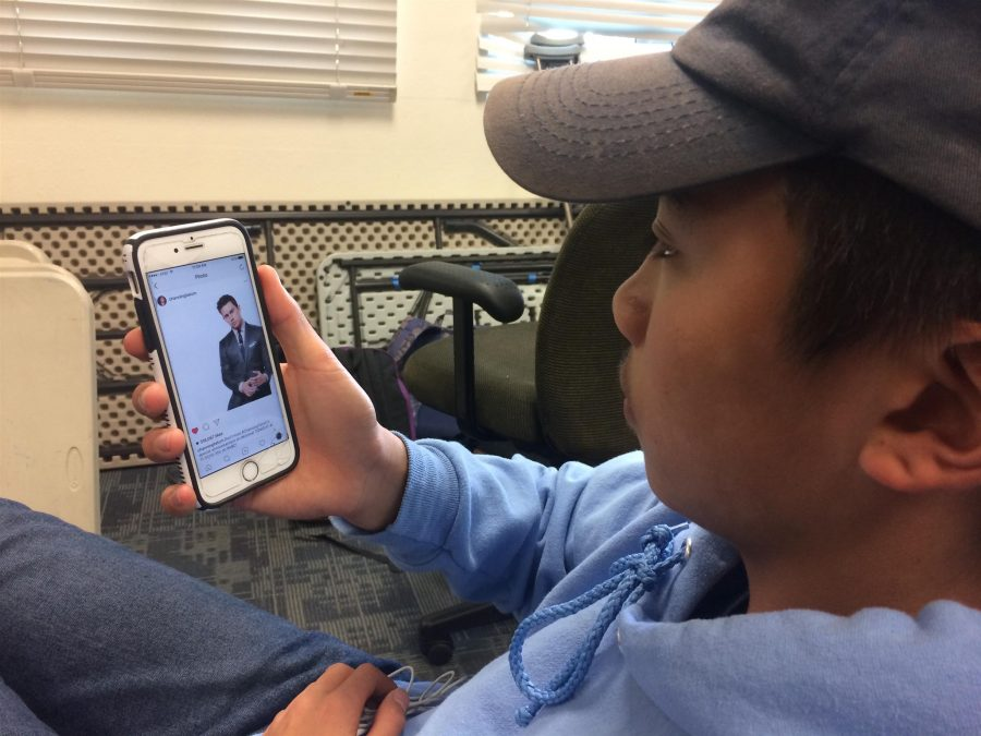 """Freshman Joe Sison observes an Instagram picture of celebrity Channing Tatum during a lunch break at Carlmont High School. Often while scrolling through social media sites there are pictures posted of famous men who fit the standards of being attractive. Sison said, """" Instagram pressures me more than any other form of social media, body types especially are displayed a lot on Instagram."""""""