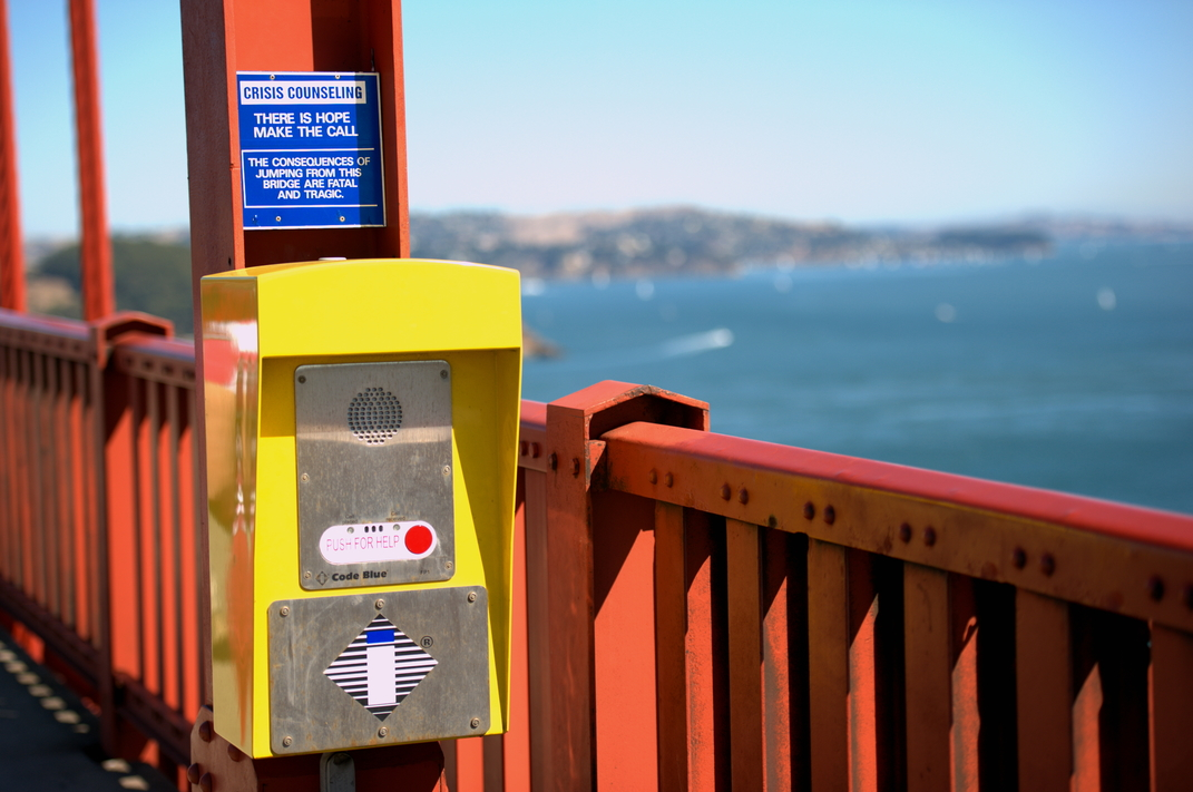 Sign and telephones hang along the Golden Gate Bridge to help stop those considering suicide from committing the act.