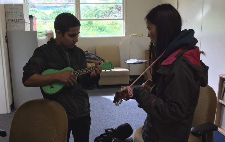 Ukulele Club members share strumming techniques during a club meeting.
