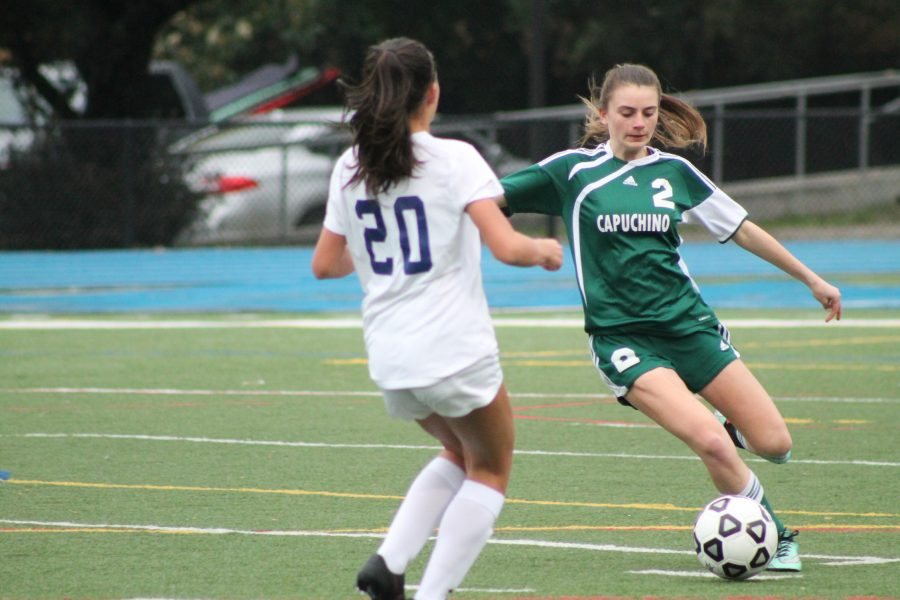 Capuchino player Lauren Meyer uses fancy footwork to dribble past Carlmont's Alexis Eliopoulos.