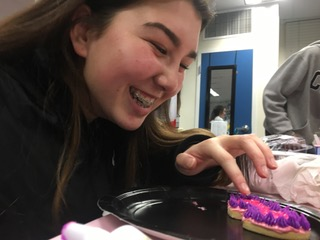 Nicole Turk decorates cookies that a student brought in to the reach out hangout event.