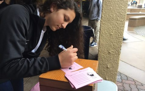 Mia Zidan, a junior, writes a note to be delivered with a rose during lunch.