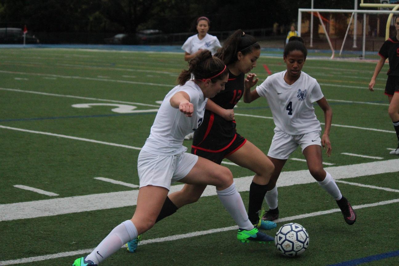 Sophomore Kayla Gustafson and freshman Rachel Chatman work together to get the ball.