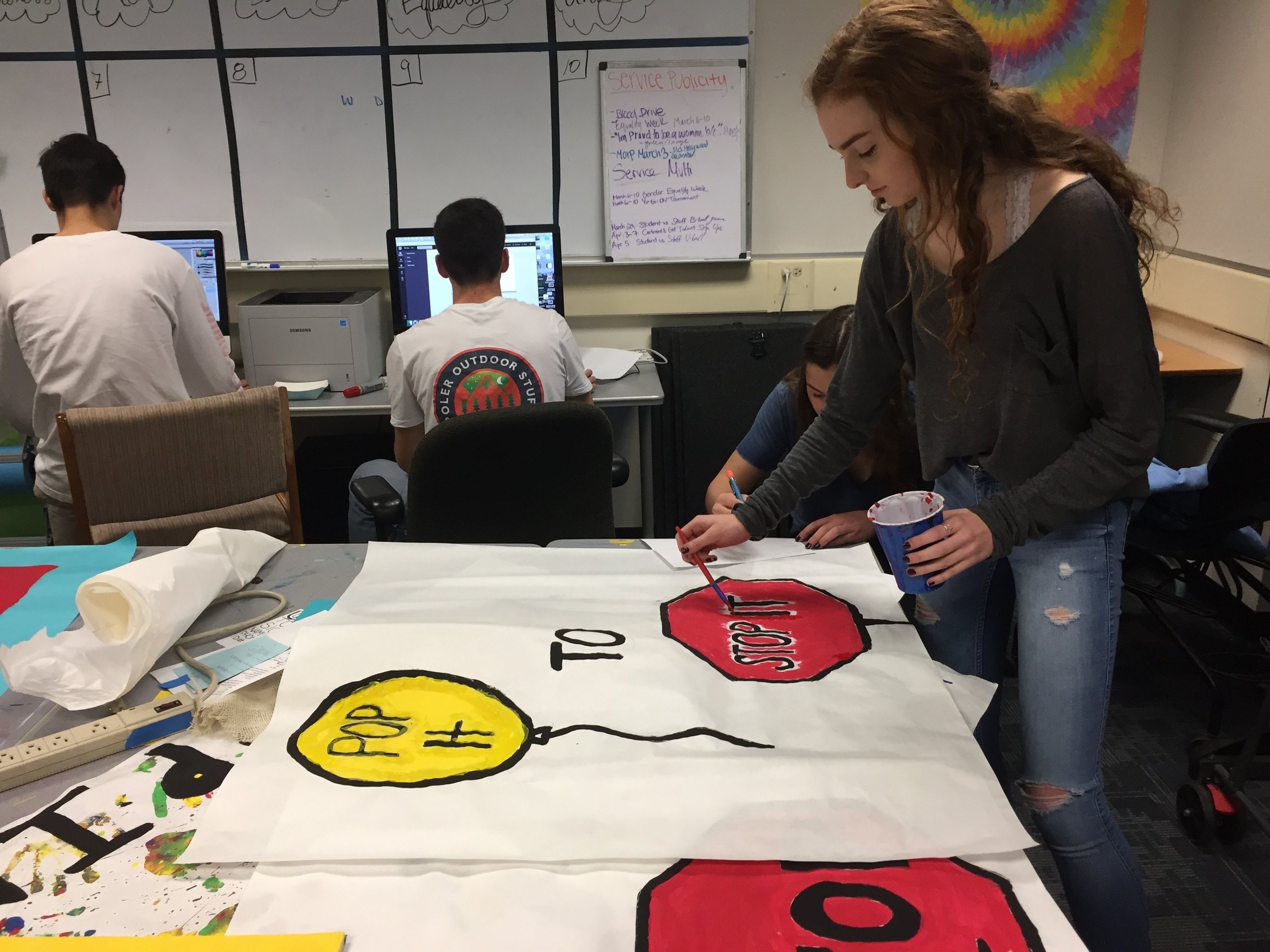 Maddie Standlee, a member of the Human Relations Commission, works on posters to spread awareness for Gender Equality Week. She paints a stop sign to advertise for the