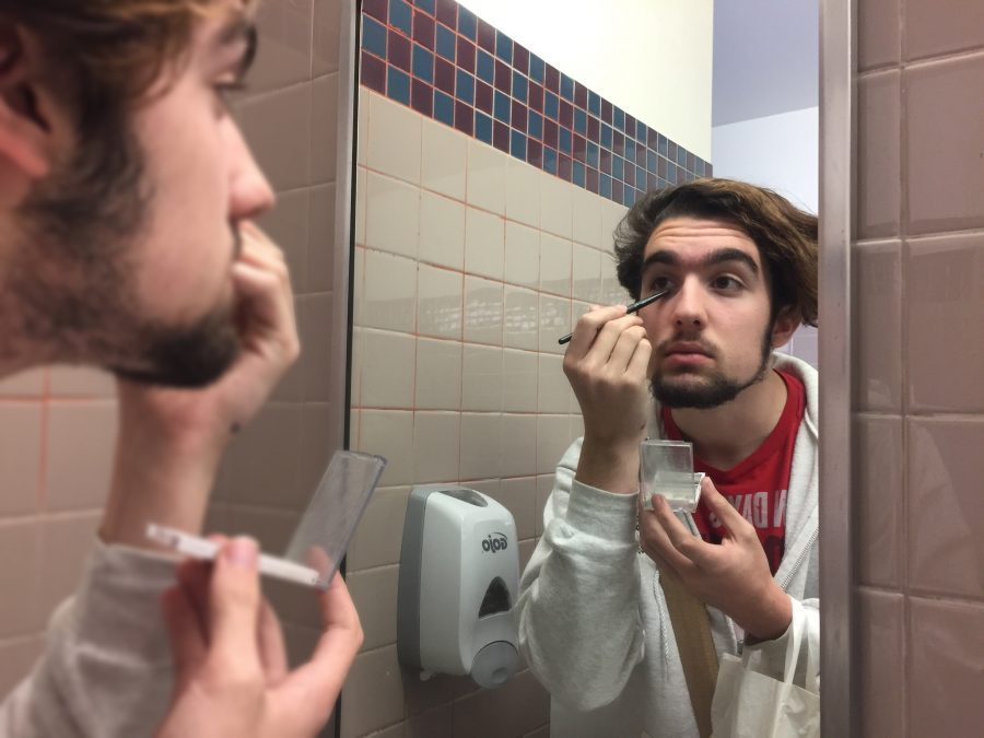 Sophomore Travis Mathers putting on makeup in the restroom.
