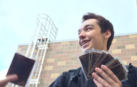 Matthew Bowker, a senior, passes the time by playing Yu-Gi-Oh! while waiting for the Carlmont performing arts center to open.