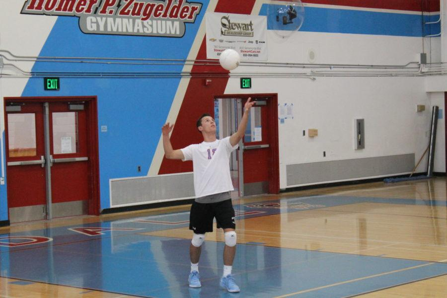 Hillsdale senior Cole Jensen serves the ball to opponent Carlmont during the match.
