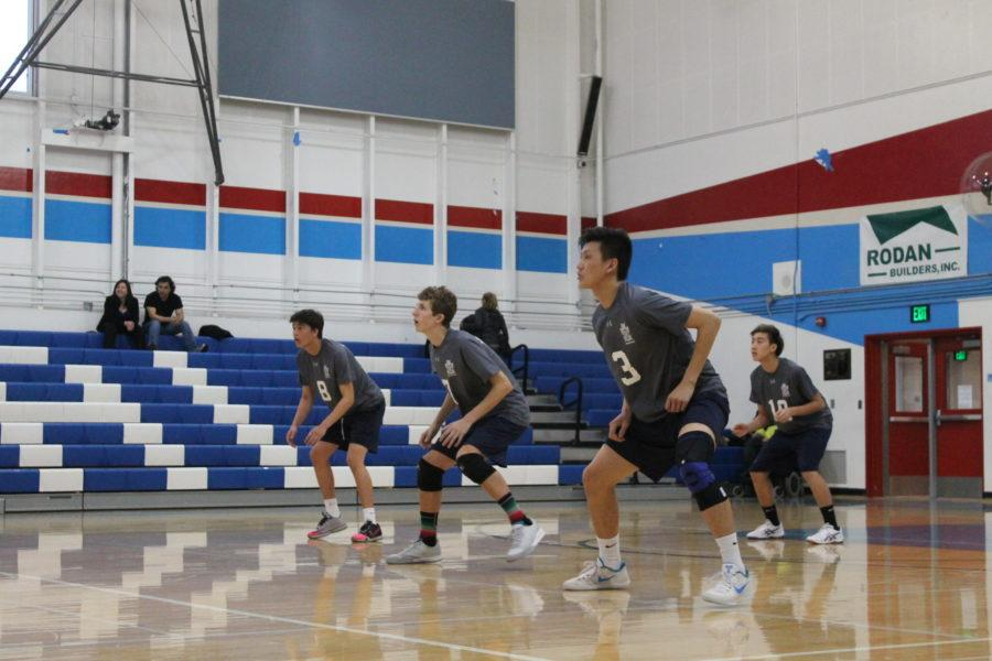 Christopher Ding, a senior, Jonah Przybyszewski, a junior, and Adam Chiu, a junior, squat in a ready stance for the serve.