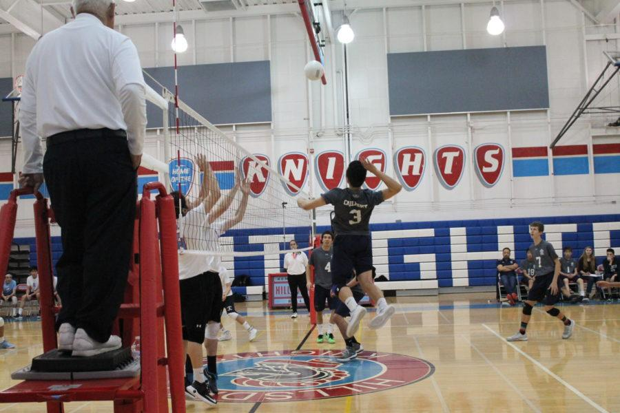Christopher Ding, a senior, jumps up to hit a ball against Hillsdale blockers.